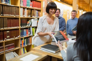 Woman tkaing out book at library desk